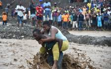 A man carries a woman across a river at Petit Goave where a bridge collapsed when Hurricane Matthew made landfall, southwest of Port-au-Prince, October 5, 2016. Picture: AFP
