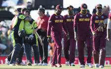 Irelands batsman John Mooney (2nd L) celebrates with teammate Niall OBrien (L) as the West Indies team (R) leaves the field after the Pool B 2015 Cricket World Cup match between Ireland and the West Indies at Saxton Park Oval in Nelson on 16 February, 2015. Picture: AFP.