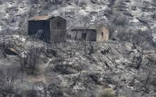 Burned houses stand amidst charred trees, following a wildfire in the forested hills of the Kabylie region, east of the Algerian capital Algiers, on August 11, 2021. Picture: Ryad Kramdi / AFP