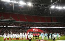 The England and Slovenia teams line up for the national anthems with an empty upper tier in the stands during the Fifa World Cup 2018 qualification football on 5 October 2017. Picture: AFP.