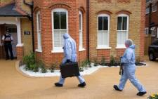 FILE: Police forensic officers enter a house in New Malden, south London, on 23 April 2014 after three children were found dead. Picture: AFP.
