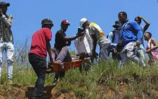 A victim of a police brutality, who was shot by Swazi Special Police Unit's Operation Service Support Unit (OSSU), is carried away on a stretcher in Mbabane, Eswatini, on 20 October 2021. Picture: AFP