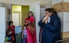 FILE: Anna (C) and Marina (R) from the Chechen Republic and their children stand in the kitchen of the refugee center in Linin, about 40 km south from Warsaw, on November 26, 2015.  Picture: AFP.