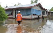 This handout photo taken and received from the Samoa Red Cross on 12 February 2018 shows a Samoa Red Cross worker checking on a house in the Apia area on a flooded street after Cyclone Gita wreaked havoc on the island. Picture: AFP
