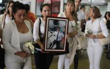 Relatives of Bolivian Fernando Ovar Goytia, wait at the ViruViru airport in Santa Cruz, Bolivia, on 2 December, 2016 for the arrival of the coffins from Medellin, Colombia, with the remains of five Bolivians killed in 28 November plane crash. Picture: AFP.