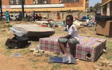 A child sits on a bed after his family was evicted by the Red Ants from their Jeppestown flat. Picture: Vumani Mkhize.