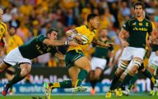 Australian fullback Israel Folau is tackled by South African scrum half Francois Louw during the Rugby Championship match at Suncorp Stadium in Brisbane on 7 September 2013. Picture: AFP/Patrick Hamilton