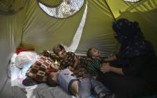 An internally displaced Afghan family, who fled from Takhar province due to battles between Taliban and Afghan security forces, sits inside their temporary tent at Sara-e-Shamali in Kabul on 11 August 2021. AFP