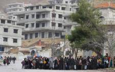 FILE: Residents of the besieged rebel-held Syrian town of Madaya wait for a convoy of aid from the Syrian Arab Red Crescent on 14 January 2016. Picture: AFP.