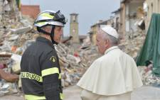 Pope Francis talks with a firefighter during a visit to the quake-hit own of Amatrice in Italy. Picture: AFP
