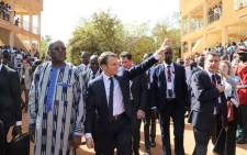 French President Emmanuel Macron (C) salutes residents, walking with Burkina Faso's President Roch Marc Christian Kabore (L), as he leaves the Ouagadougou University after giving a speech on 28 November 2017 in Ouagadougou, as part of his first African tour since taking office. Picture: AFP.