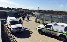 Forensics experts and detectives are on the scene of a suspected mob attack in the Heideveld area in Cape Town where the charred bodies of two men which have been partially covered in blue plastic bags lie at the bottom of the bridge on 6 July 2015. Siyabonga Sesant/EWN.