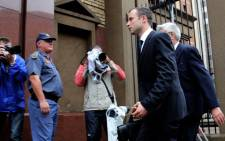 Oscar Pistorius is escorted into the North Gauteng High Court in Pretoria ahead of his murder trial on 12 March 2014. Picture: Sebabatso Mosamo/EWN.