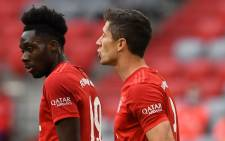 Bayern Munich's Canadian midfielder Alphonso Davies (L) and Bayern Munich's Polish forward Robert Lewandowski react during the German first division Bundesliga football match FC Bayern Munich v Fortuna Duesseldorf on 30 May 2020 in Munich, southern Germany.