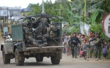 Philippine troops escort rescued civilians while a military truck covers them from sniper fire at a village on the outskirts of Marawi on the southern island of Mindanao. Picture: AFP