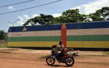 "FILE: A man rides a motorbike in front of the jail of Bangui, ""Maison Centrale de Ngaragba"", whose walls are painted with the colors of the flag of Central African Republic. Picture: AFP"