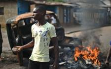 FILE:A protester opposed to Burundian President Pierre Nkurunziza's third term brandishes a rock as he stands beside a burning vehicle during a demonstration in the Buyenzi neighborhood of Bujumbura on 26 May, 2015. Picture: AFP.