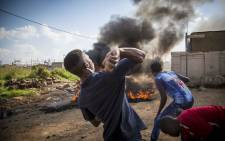 A protester hurls a rock at police during skirmishes over service delivery in Olievenhoutbosch. Picture: Thomas Holder/EWN