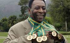 Brazilian football legend Edson Arantes do Nascimento, known as 'Pele', poses with his six Brazil's champion medals on December 22, 2010 during a ceremony in Rio de Janeiro, Brazil. Picture: AFP