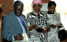 Zimbabwe President Robert Mugabe (L) casts his vote by his wife Grace and daughter Bona (R) at a polling booth in a school in Harare on July 31, 2013. Picture: AFP.