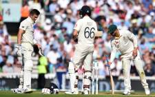 England's Joe Denly (L) gestures after being hit by a ball in the midriff as England's captain Joe Root (C) looks on during play on the third day of the fifth Ashes cricket Test match between England and Australia at The Oval in London on 14 September 2019.