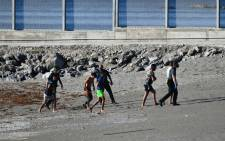 Migrants speak with Spanish Civil guards after swimming to the Spanish enclave of Ceuta from neighbouring Morocco on May 17, 2021. Antonio Sempere / AFP
