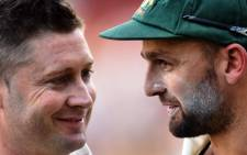 Australia's captain Michael Clarke speaks with spin bowler Nathan Lyon (R) after beating India on the final day of the first cricket test match between Australia and India at the Adelaide Oval on 13 December, 2014. Picture: AFP.