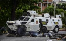 A National Guard vehicle goes through a barricade built by anti-government activists in Venezuela's third city, Valencia, on 6 August 2016, a day after a new assembly with supreme powers and loyal to President Nicolas Maduro started functioning in the country. Picture: AFP