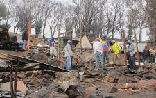 A man rebuilds his home following a deadly shack fire in Mandela Park. Picture: Georgina Selander/EWN
