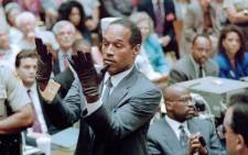 OJ Simpson looks at a new pair of Aris extra-large gloves which the prosecutors had him put on for the jury 21 June 1995 during his double murder trial in Los Angeles. The gloves were the same type found at the Bundy murder scene and the OJ Simpson estate. Picture: AFP