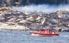 Rescue forces work at the shore west of Bergen, Norway after a helicopter transporting 13 workers from an offshore oil field in the North Sea crashed off on 29 April, 2016. Picture: AFP.