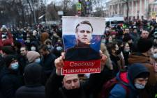"Protesters march in support of jailed opposition leader Alexei Navalny in downtown Moscow on 23 January 2021. The placard with an image of the Kremlin critic reads ""Freedom to Navalny!"". Picture: Kirill KUDRYAVTSEV/AFP"