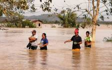 Residents wade through a flooded highway, caused by heavy rains due to Typhoon Phanfone, in Ormoc City, Leyte province in central Philippines on 25 December 2019. Picture: AFP