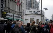 Tourists pose for pictures at the former Allies' checkpoint at Checkpoint Charlie in Berlin, on October, 24 2011, where a plaque commemorates the 50th anniversary of the October 1961 standoff of Soviet and American tanks at the famous Cold War border crossing. Picture: AFP.