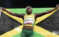 Jamaica's Elaine Thompson-Herah celebrates with the flag of Jamaica after winning the women's 100m final during the Tokyo 2020 Olympic Games at the Olympic Stadium in Tokyo on July 31, 2021. Piture: Javier SORIANO / AFP