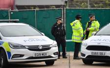 British Police officers stand on duty at a cordon near to where a lorry, believed to have originated from Bulgaria, and containing 39 dead bodies, was discovered at Waterglade Industrial Park in Grays, east of London, on 23 October 2019. Picture: AFP