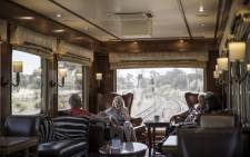 Blue Train passengers enjoy drinks in the observation car as the train slowly makes its way through the outskirts of Cape Town, on 25 February 2021. Picture: MARCO LONGARI/AFP
