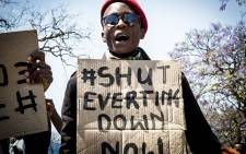 A demonstrating #FeesMustFall member holds up a placard during protests over tertiary education fees in Pretoria on 10 October 2016. Picture: Reinart Toerien/EWN.