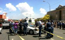 Police gather around a vehicle hit by a Nyala carrying Jasmin Pretorius's uncle out of the Brakpan Magistrates Court, 13 January 2014. Picture: Mia Lindeque/EWN.