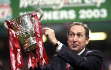 FILE: Liverpool's French manager Gerard Houllier holds the cup aloft celebrating victory over Manchester United in the Worthington Cup Final at the Millenium stadium in Cardiff 2 March 2003. Picture: AFP