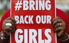 "FILE: Around 60 people in red T-shirts that read ""Bring Back Our Girls"" marched to residence of Goodluck Jonathan. Picture: AFP."
