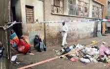 Mothers and guardians of three children who were killed in a wall collapse in Doornfontein sit weeping. Picture: Katleho Sekhotho/EWN.