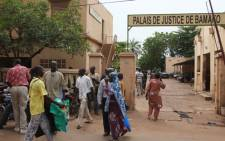 """People walk in front of the 'Palace of Justice' courthouse in Bamaka, on August 28, 2012. A Bamako court today handed three men a six months suspended sentence for a brutal attack on interim President Dioncounda Traore during a protest by those opposed to his appointment on May 21. Boubacar Bore, Yacouba Niare and Mamadou Sangare who were accused of being involved in the attack were found guilty of """"serious disturbances to public order"""". Another three men who were accused of organising the protest during which Traore was attacked, were also given a six months suspended sentence for their role in the disturbances. Picture: AFP."""