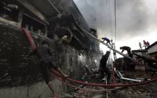 Bangladeshi firefighters and volunteers work to put out a fire and search for survivors at the site of an explosion in a factory in the key Bangladeshi garment manufacturing town of Tongi. Picture: AFP.