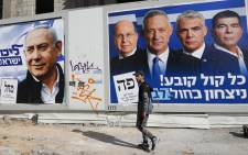 FILE: A man walks past electoral campaign posters bearing the portraits of Israel's Prime Minister Benjamin Netanyahu (L), leader of the Likud party, and retired Israeli general Benny Gantz (R), one of the leaders of the Blue and White (Kahol Lavan) political alliance, in the Israeli city of Tel Aviv, on 3 April 2019, ahead of the general election scheduled for 9 April. Picture: AFP