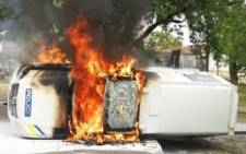 FILE: A police vehicle set alight by angry farmers outside the Senekal Magistrate's Court on 6 October 2020. Picture: @crimeairnetwork/Twitter