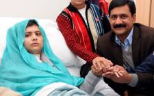 Malala Yousafzai, who was shot in the head by Taliban gunmen for campaigning for the right to an education, sits with her family in hospital. Picture: AFP