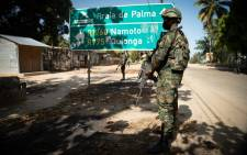 A Rwandan soldier walks in front of a burned truck near Palma, Cabo Delgado, Mozambique on 22 September 2021. Since July 2021 a contingent of a thousand Rwandan soldiers and policemen is deployed to Mozambique to fight insurgents that were terrorising populations. The Rwanda Defence Forces (RDF) declared few victories among which the liberation of Mocimboia Da Praia which was occupied by jihadist for almost a year. Picture: AFP
