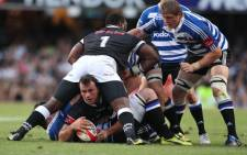 Bismarck du Plessis (L, down) of the Durban Sharks holds onto the ball during their Currie Cup Final match against Western Province. Picture: AFP