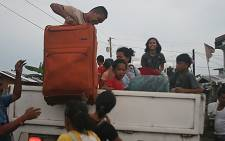 FILE:Residents carry their belongings onto a government vehicle as they evacuate from their tent houses to a safer place in Tacloban City, central Philippines on 4 December 4, 2014, ahead of the landfall of super Typhoon Hagupit. Picture: AFP.